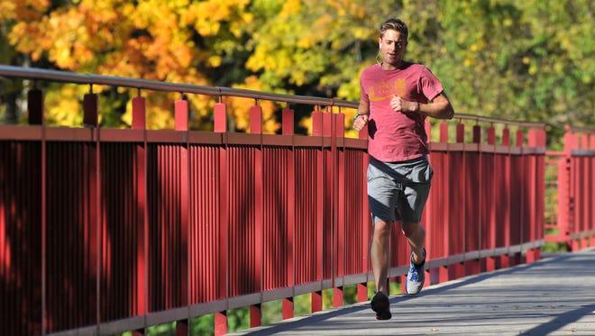 A jogger crosses the Monon Trail bridge over the White River north of Broad Ripple.