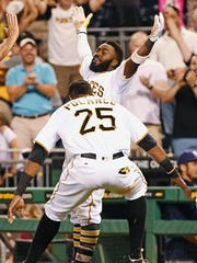 Pittsburgh Pirates second baseman Josh Harrison (5) and right fielder Gregory Polanco (25) celebrate a victory after Harrison scored the winning run in the bottom of the ninth inning after a baseball game against the Milwaukee Brewers in Pittsburgh, Tuesday, July 19, 2016.