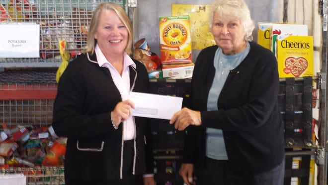 Robin Ervin of Coldwell Banker Realtors and the Hunterdon Somerset Associaton of Realtors presents  Marie Scannell, Executive Director of The Food Bank Network of Somerset County with a check for $1,832.