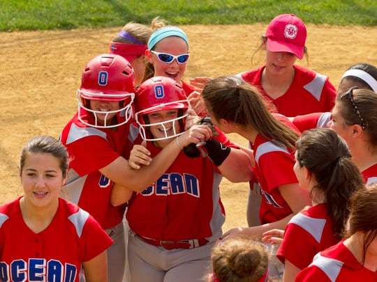 Ocean's Morgan Walsh is surrounded by teammates as they celebrate after the first of two home runs against Wall on Wednesday.