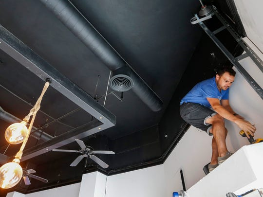 Micah Pope, owner of The Wine Dive, gets ready to install a speaker at the space that was held the Blue Bull restaurant on Park Central Square. The new wine bar is expected to open between August and October.
