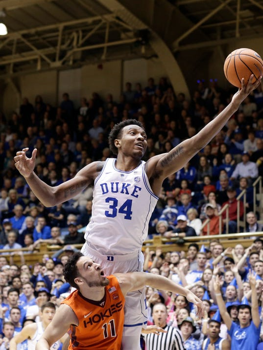 FILE - In this Feb. 14, 2018, file photo, Duke's Wendell Carter Jr. (34) shoots against Virginia Tech during the first half of an NCAA college basketball game, in Durham, N.C. Bank records and other expense reports that are part of a federal probe into college basketball list a wide range of impermissible payments from agents to at least two dozen players or their relatives, according to documents obtained by Yahoo Sports. Yahoo said Friday, Feb. 23, 2018, that the documents obtained in discovery during the investigation link current players including Michigan State's Miles Bridges, Duke's Wendell Carter and Alabama's Collin Sexton to potential benefits that would be violations of NCAA rules. (AP Photo/Gerry Broome, File)