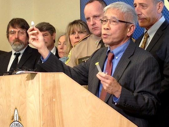 Dr. Harry Chen, state health commissioner, holds a dose of naloxone, a drug that can reverse the effects of a heroin or opiate overdose, during a news conference earlier this year in Waterbury as Col. Tom L'Esperance, director of the Vermont State Police, and Gov. Peter Shumlin are among the crowd looking on.