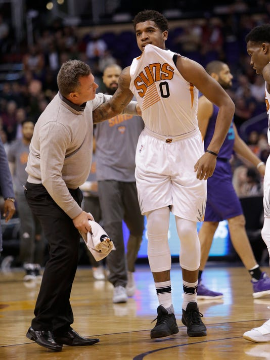 Phoenix Suns forward Marquese Chriss (0) is helped off the court by a trainer in the first quarter during an NBA basketball game against the Charlotte Hornets, Thursday, March 2, 2017, in Phoenix. (AP Photo/Rick Scuteri)