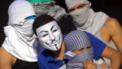 Palestinian demonstrators stand during clashes with