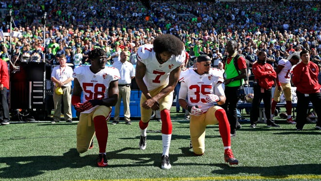 49ers Eli Harold (58), Colin Kaepernick (7) and Eric Reid (35) drop to a kneeling position at the beginning of the national anthem before their game against the Seahawks on Sept. 25.