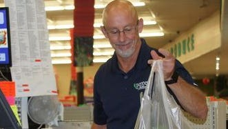 Mark Schultze runs the register during a busy day at peppers Supermarket.