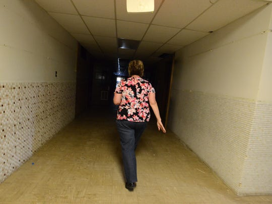 Anna Tobin, executive director of Meals on Wheels Older Adult Alternatives of Fairfield County, walks through a darkened hallway of the old Cedar Heights Elementary Wednesday, May 23, 2018, in Lancaster. The building is currently undergoing renovations to be turned into the agency's new home.