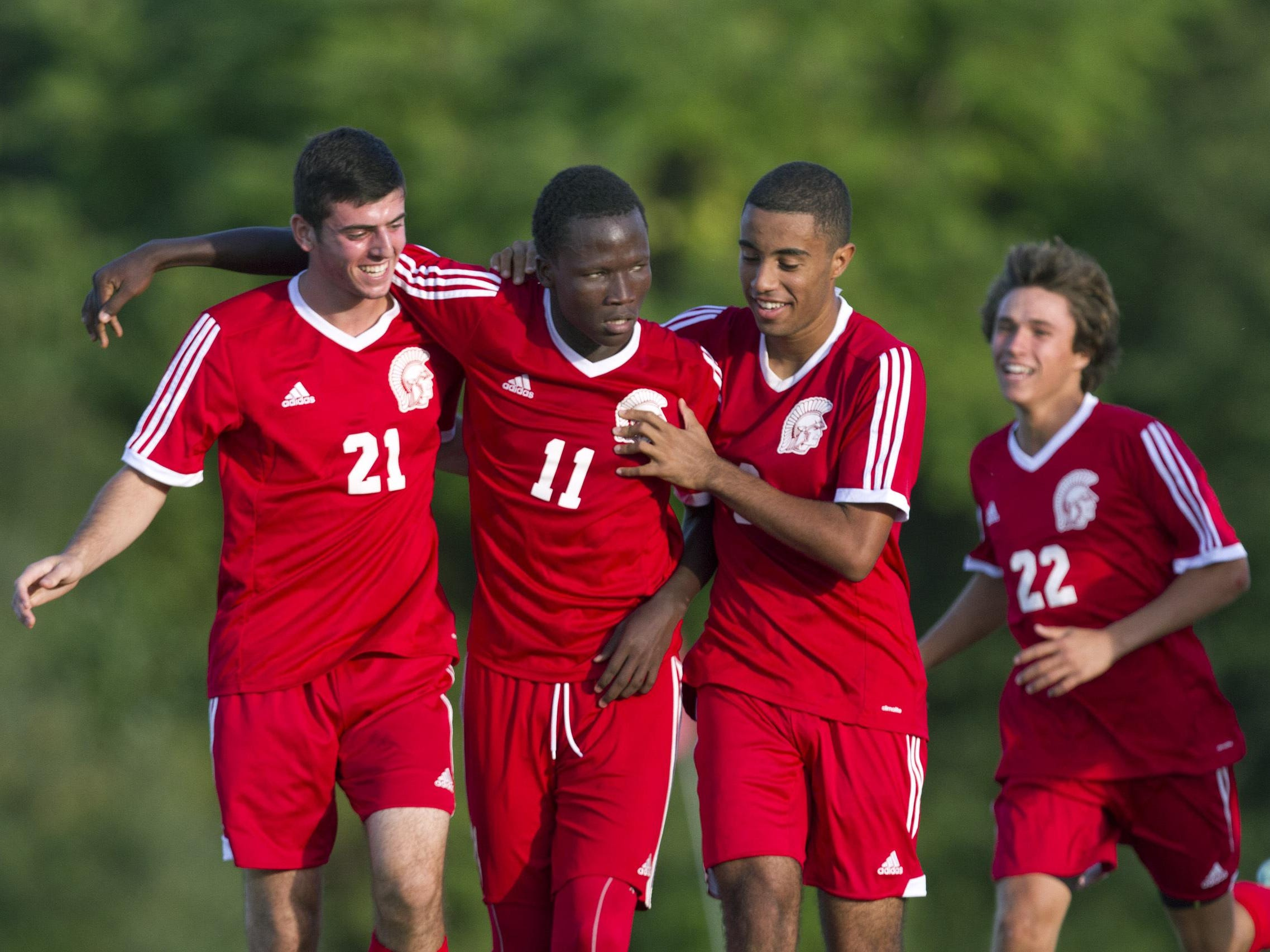Ocean's Marlhens Nasenes is mobbed by team mates after scoring the winning goal minutes into overtime to break the 1-1 tie with Colts Neck. Ocean vs Colts Neck Boys Soccer in Colts Neck, NJ on September 24, 2015.