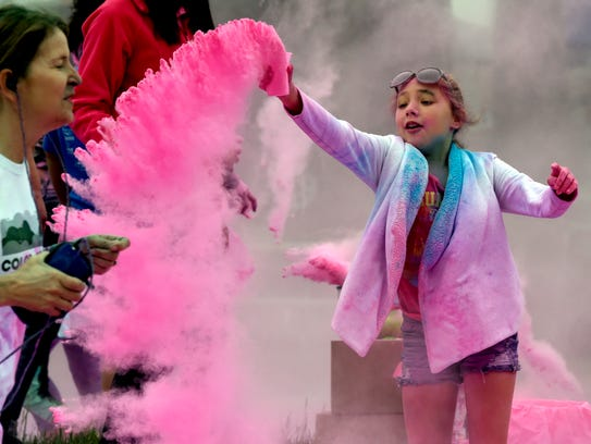 Gianna Robinson, 10, of Evansville tosses some pink-colored