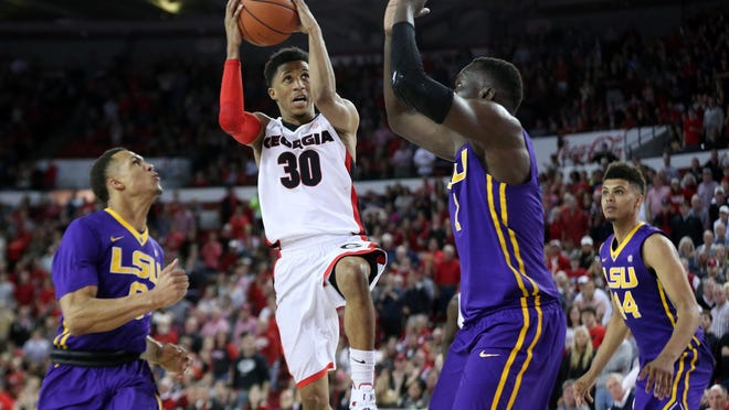 Georgia Bulldogs guard J.J. Frazier (30) draws a foul in the final seconds of the game against LSU Tigers guard Brandon Sampson (0) and forward Duop Reath (1) during the second half at Stegeman Coliseum. UGA defeated LSU 82-80.