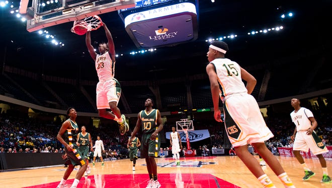 Carver's Brandon Austin (23) dunks as Woodlawn's DeCarlos Wright (10) looks on during the AHSAA Class 6A State Semi Final game on Thursday, Feb. 26, 2015, in Birmingham, Ala.