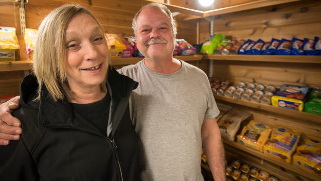 Howard and Lori Sandler, owners of Sandler's Party Store in Fort Gratiot, stand inside the former humidor inside of the store Thursday, March 29. The humidor has been turned into a pantry for the Ben and Zoe Project, a program offering free food and supplies for dogs and cats.