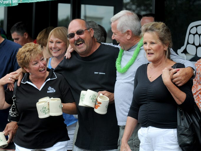 Members of the Greene Turtle Mug Club share a laugh in front of the old location before parading their mugs to the location at the Centre of Salisbury Sunday afternoon.
