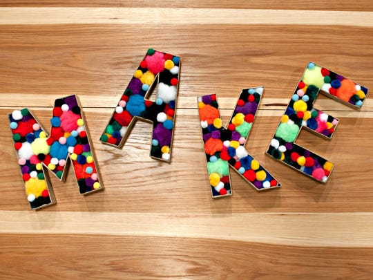 Papier-mache letters with fronts removed are filled with colorful pom-poms.