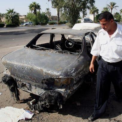 A 2007 photo shows an Iraqi traffic policeman inspecting