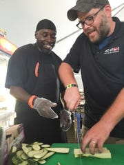 Rodney Perkins (left) works at the catering tent with Jonathan Dye, a culinary director at Red Frog.