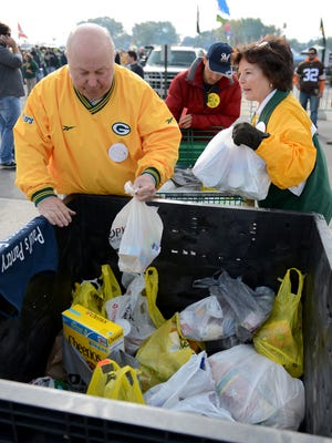 Volunteers Bob Peters and Helen Falk collect food for the Packers Women's Association's annual food drive for Paul's Pantry in Green Bay outside Lambeau Field in 2013.