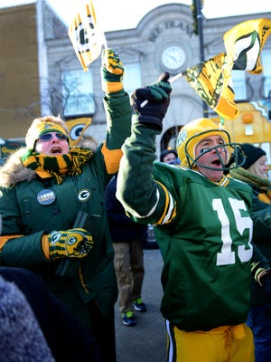 Packers fans Ginger Kerkhoff and Bart Boyden cheer during Friday's pep rally in downtown Green Bay.