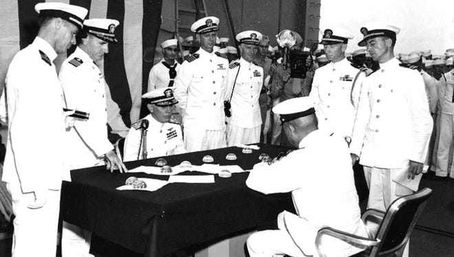 Aboard the USS Portland, Vice Admiral Chiuchi Hara, Commander, 4 th Fleet, signs the document surrendering the base at Truk, Caroline Islands on 2 September 1945. US Navy officers around the table are, left to right: Lt. S.E. Thompson, USNR, Flag Lieutenant; Captain O.F. Naquin, USN, Acting Chief of Staff; Vice Admiral George D. Murray, USN, Commander, Marianas (seated), accepting the Japanese surrender on behalf of the Commander in Chief, Pacific Fleet and Pacific Ocean Areas; Capt. D.N. Cone, USN, representing Commander, the Marshalls and Gilberts Islands; Capt. L.A. Thackery, USN, Commanding Officer, USS Portland; Lt. L.L. Thompson, USN, Flag Secretary; and Lt. A. M. Soden, USNR, interpreter.