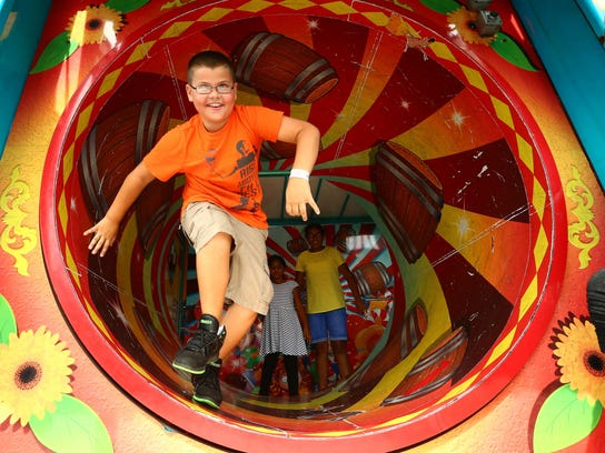 A youngster exits the barrel roll at a fun house at