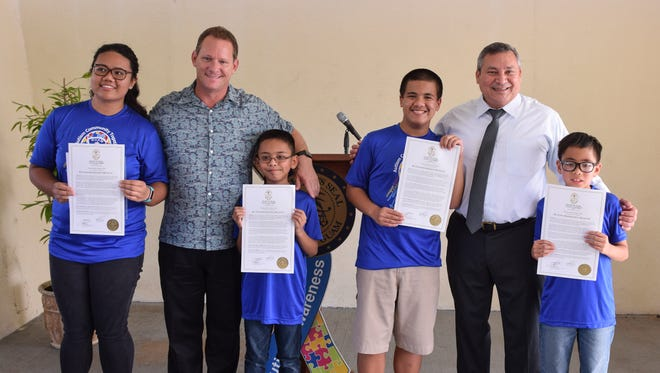 A proclamation signing ceremony was held to recognize April as Autism Awareness Month at the Ricardo J. Bordallo Governor's Complex on April 2, 2018. From left: Gianna Lynn Palmares, 19, Lt. Gov. Ray Tenorio, Connor Rodriguez, 10, Zachary Zanoni, 15, Gov. Eddie Baza Calvo, and Tristain Merfalen, 8.