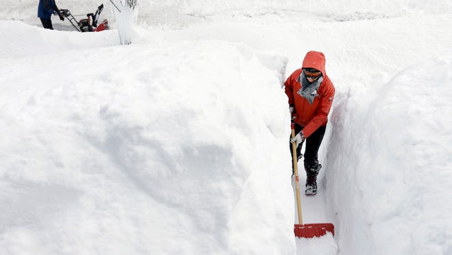Kim Taylor, of Norwood, Mass., right, shovels a path in the snow in front of her home Sunday, Feb. 15, 2015, in Norwood. A storm brought a new round of wind-whipped snow to New England on Sunday, threatening white-out conditions in coastal areas and forcing people to contend with a fourth winter onslaught in less than a month. (AP Photo/Steven Senne)
