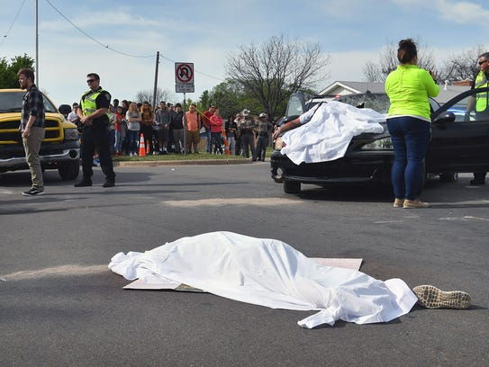 A mock drunk driving accident scene features two Rider
