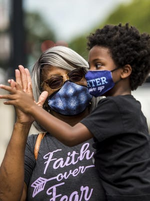 Sonya Cobb gets some high-fives from her grandson, Jahneh Simpkins, 5, in downtown Augusta, Ga., Monday morning August 3, 2020.