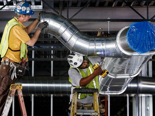 Contractors Mike Davis, left, and Tracy Woodall install duct work at the University of Memphis' new 62,000-square-foot men's basketball training facility on the Park Avenue campus.