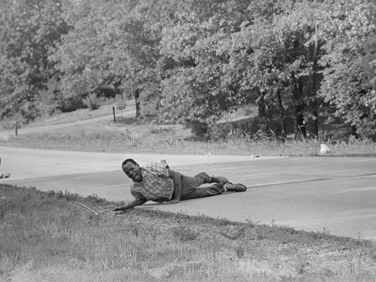 Civil rights activist James Meredith grimaces in pain as he pulls himself across Highway 51 after being shot in Hernando, Miss., on June 6, 1966. Meredith, who defied segregation to enroll at the University of Mississippi in 1962 completed the march from Memphis, Tenn., to Jackson, Miss., after treatment of his wounds.