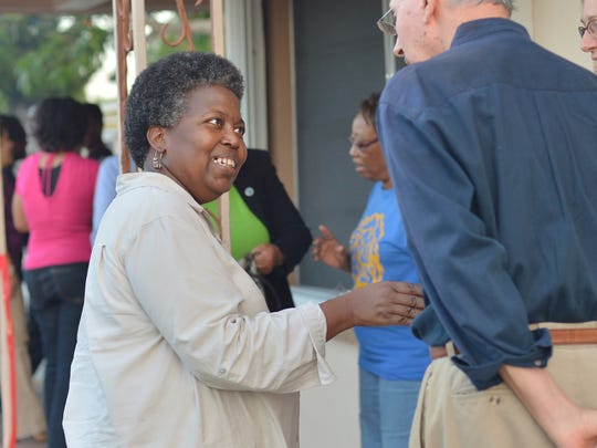 Ollie Harvey (center), program administrator of Building Bridges to Youth, smiles as she welcomes guests Dec. 20, 2012, to the dedication ceremony for the organization's new location at 720 Church St. in Stuart on Thursday.