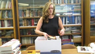 Preparing a mountain of books for the Myerstown Community Library Book and Bake Sale is Assistant Librarian Jamie Arehart.