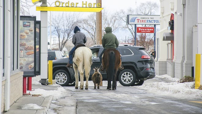Trajen Collins, left, is joined by Joel Perez as they ride their horses through the McDonald's drive-thru with a pet goat in tow in Powell, Wyo., on Dec. 30 The boys said they were bored during the holiday break and decided to ride their horses to town. The goat just followed, they said.