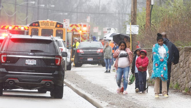 A family leaves the scene of a crash involving a school bus and multiple vehicles on Winton Road Monday.