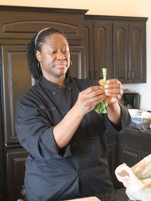 Chef Hardette Harris shows how to remove the stems from greens at one of her cooking demonstrations.