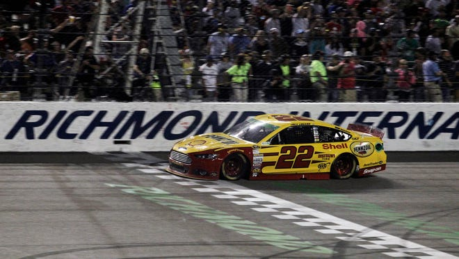 Sprint Cup driver Joey Logano (22) crosses the finish line to win the Toyota Owners 400 at Richmond International Raceway after passing three other cars on the low side in a nine-lap sprint to the finish.