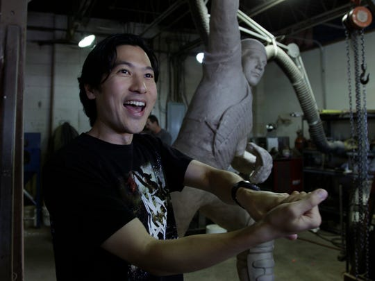 Cincinnati Sculptor Tom Tsuchiya poses in front of one of his statues.