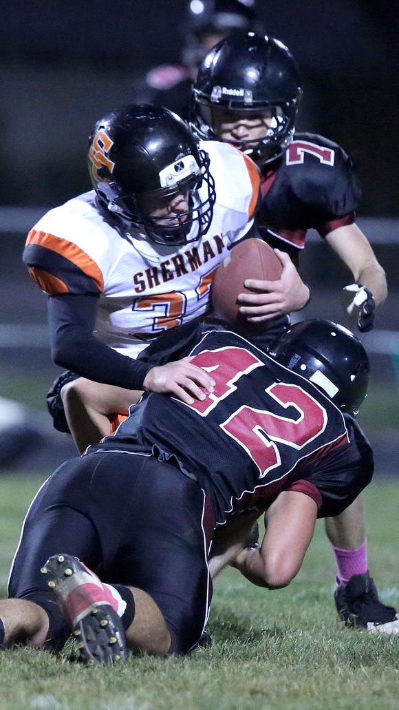 Perrydale's Keenan Bailey (42) tackles Sherman's Wyatt Stutzman (33) during the first quarter of their football game on Friday, Oct. 23, 2015, in Perrydale, Ore.