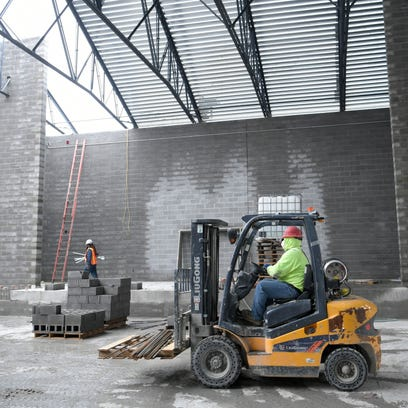 Construction crews work on the auditorium at the new
