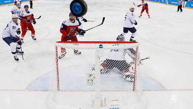 The puck flies over the goal behind USA goaltender Ryan Zapolski.