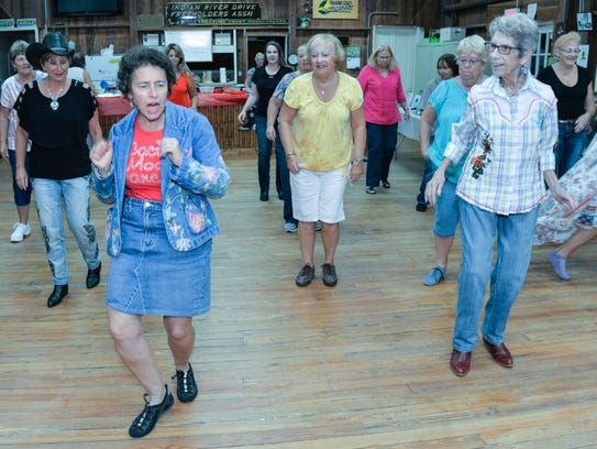 Sandy Dworkin, foreground, leads a line dance at the