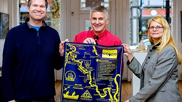 Chemung River Friends Executive Director Jim Pfiffer, center, shows off a bandanna printed with a map of the Chemung River, along with Chris Walters, left, from the ARTS Council of the Southern Finger Lakes and artist Diane Brownell.