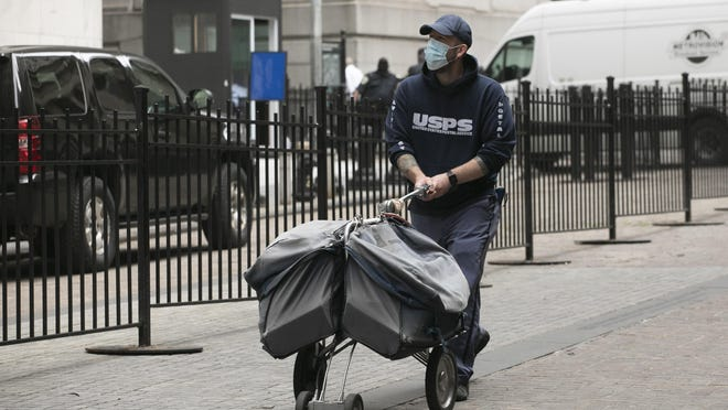 A masked postal worker pushes a cart of mail as he makes his rounds in New York during the coronavirus pandemic. Support for the U.S. Postal Service is part of the proposed HEROES Act.