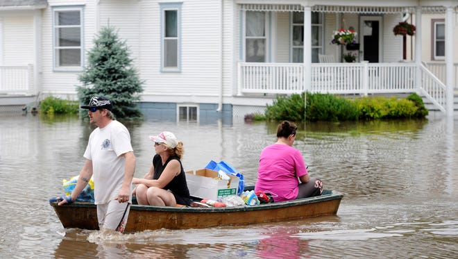 David Dixon pulls Heather Dixon and Dawn Suhr in a boat down Main Street in Rock Valley, Iowa, Tuesday afternoon, June 17, 2014, after removing some valuables from their flooded  houses. A thunderstorm on Monday dropped several inches of rain over the already saturated region causing flooding along the Rock River.