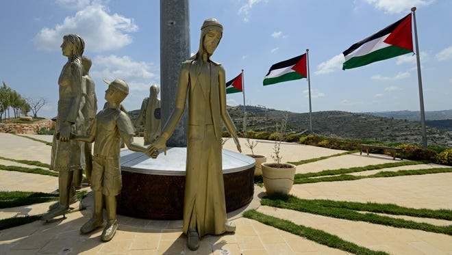 Palestinian national flags fly above statues of a Palestinian family outside the Rawabi visitor's center located on a hill overlooking the site.