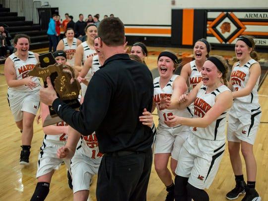 The Marine City High School girls basketball team celebrates its district championship.