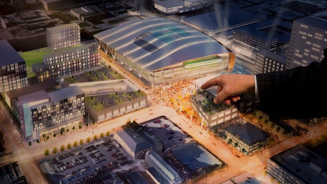 A representative of the Milwaukee Bucks points to a rendering of a new arena proposed during a press conference on Wednesday in Milwaukee.
