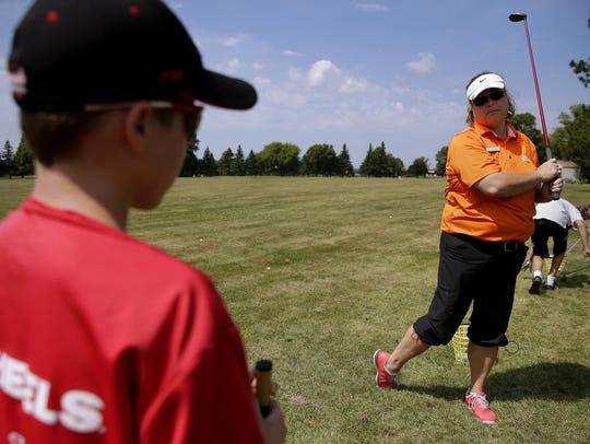 Zachary Fruendt, 10, listens to golf instructor Laura