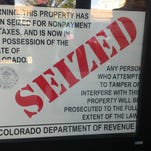 Signs in windows of the Lodge Sasquatch Kitchen in Old Town Fort Collins say that the restaurant has been seized for owners' nonpayment of state sales tax.
